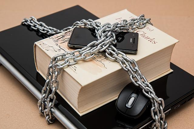 Notebook, kniha a mobil zaviazané reťazou.jpg